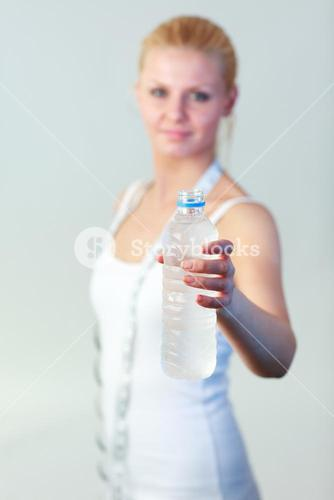 Friendly woman holding a bottle of water with focus on water