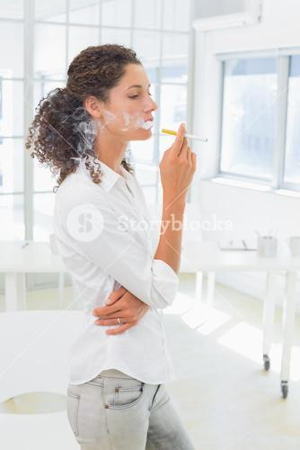 Casual businesswoman smoking an electronic cigarette