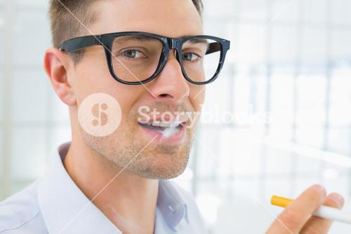 Casual businessman smoking an electronic cigarette