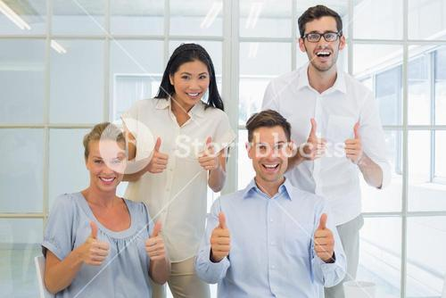 Casual business team showing thumbs up to camera