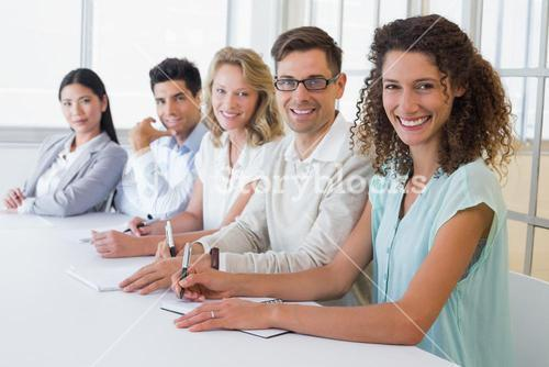 Casual business team smiling at camera sitting at desk