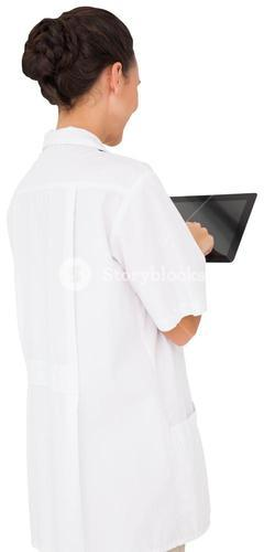 Pretty brown haired nurse using tablet pc