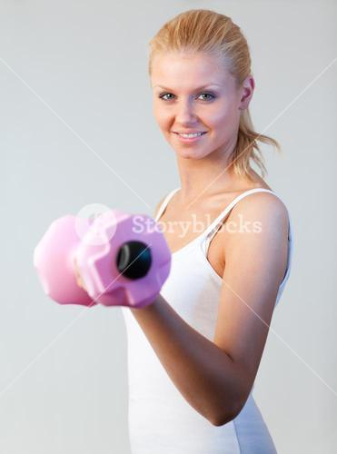 Portrait of a friendly woman trained with weights focus on woman