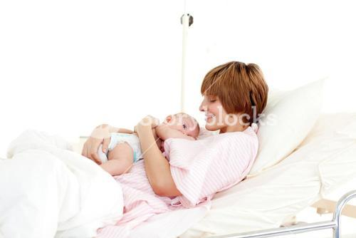 Smiling patient with newborn baby in bed