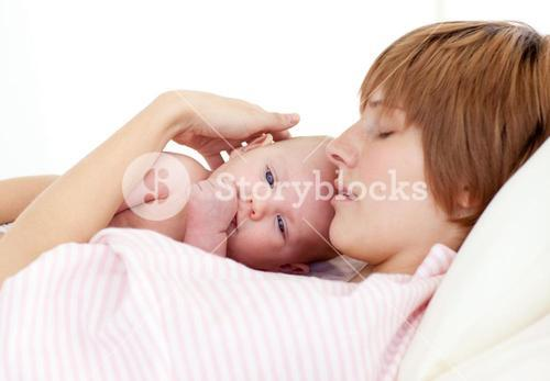 Mother sleeping with her newborn baby