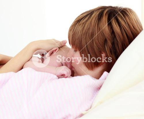 Portrait of a patient kissing her newborn baby in bed