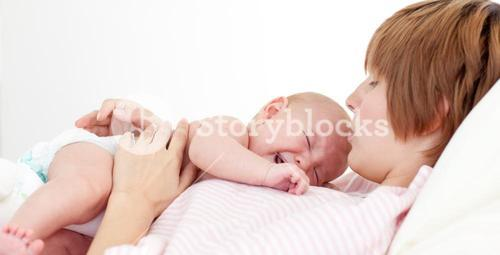 Happy mother kissing her newborn baby