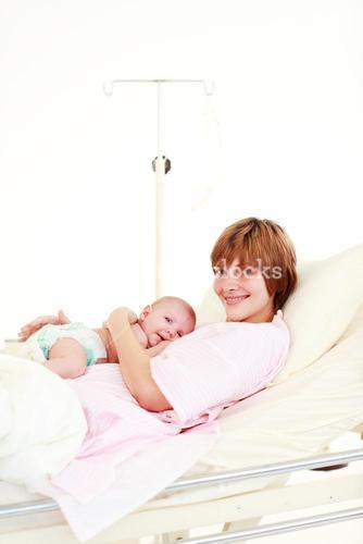 Patient with newborn baby in bed with copyspace