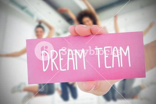 Woman holding pink card saying dream team