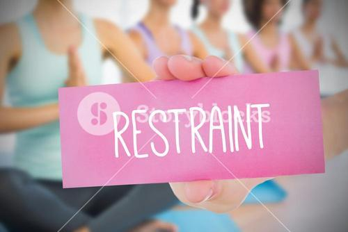 Woman holding pink card saying restraint