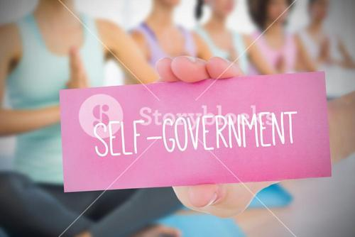 Woman holding pink card saying self government