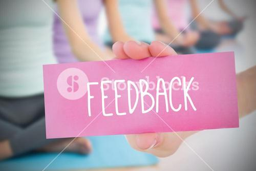 Woman holding pink card saying feedback