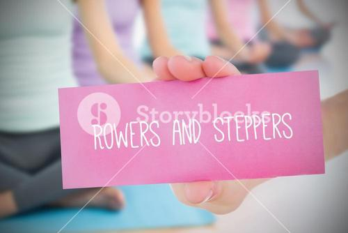 Woman holding pink card saying rowers and steppers