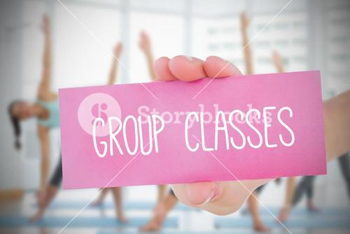 Woman holding pink card saying group classes