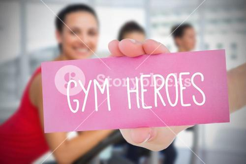 Woman holding pink card saying gym heroes