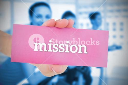 Woman holding pink card saying mission