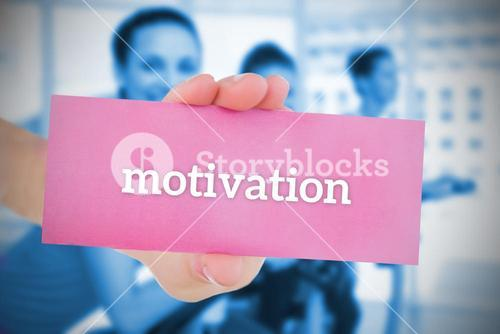 Woman holding pink card saying motivation