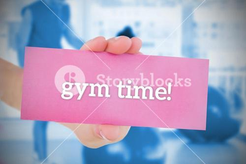 Woman holding pink card saying gym time