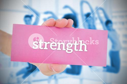 Woman holding pink card saying strength
