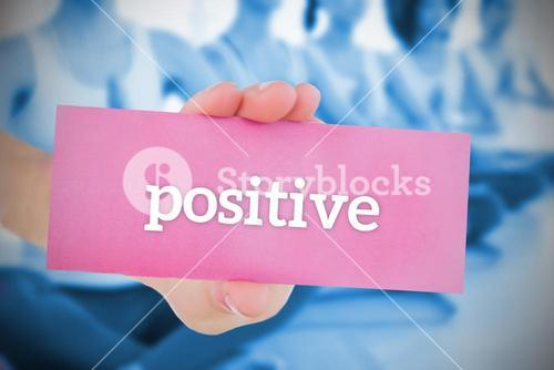 Woman holding pink card saying positive