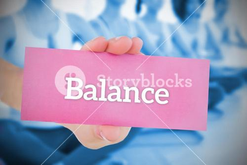 Woman holding pink card saying balance