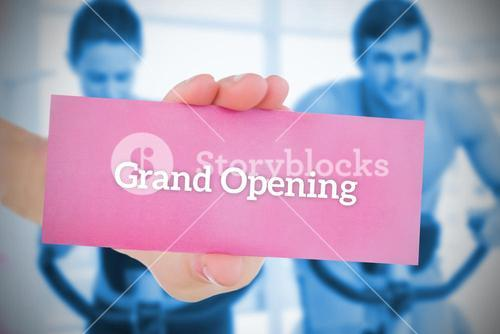 Woman holding pink card saying grand opening