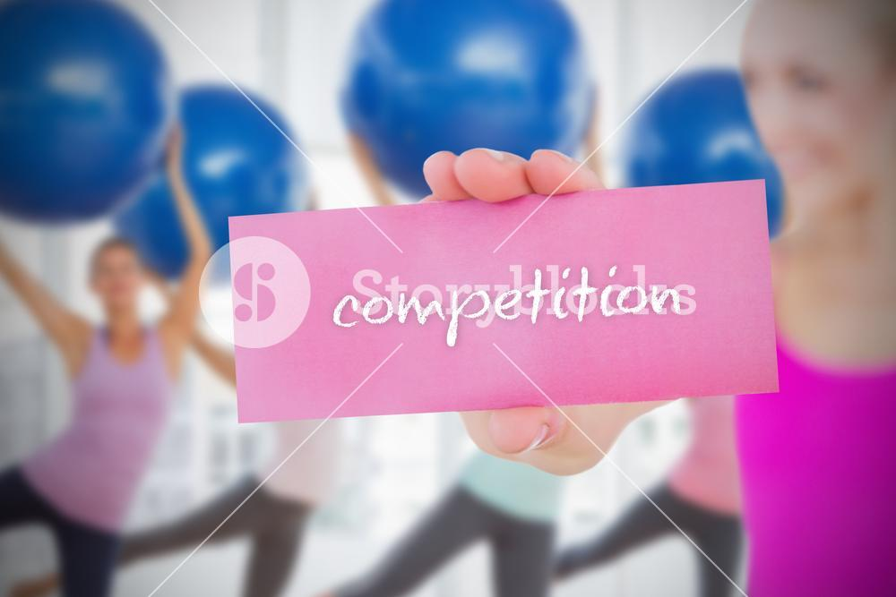 Fit blonde holding card saying competition