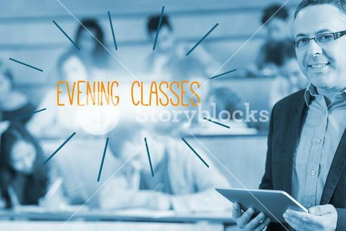 Evening classes against lecturer standing in front of his class in lecture hall
