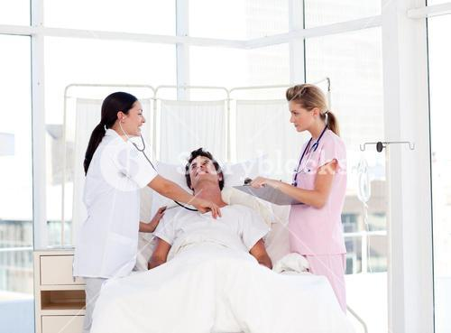 Female doctor and nurse looking after a patient