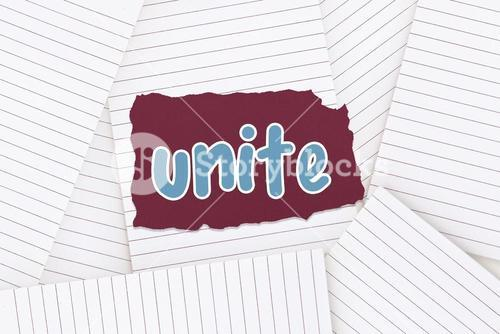 Unite against lined paper strewn over surface