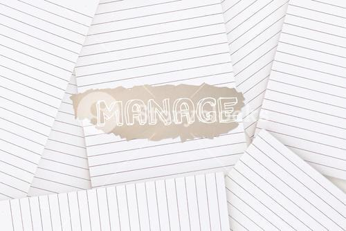 Manage against lined paper strewn over surface