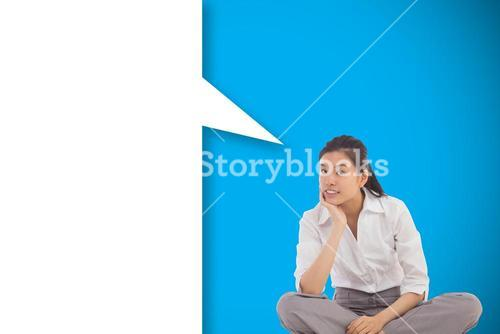 Composite image of businesswoman sitting cross legged thinking with speech bubble