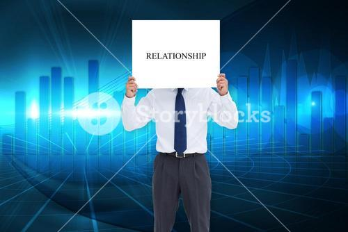 Businessman holding card saying relationship