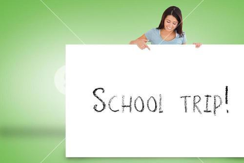 Pretty brunette showing card with school trip