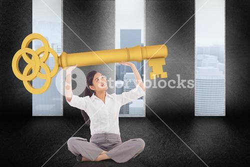 Composite image of businesswoman sitting cross legged carrying large key