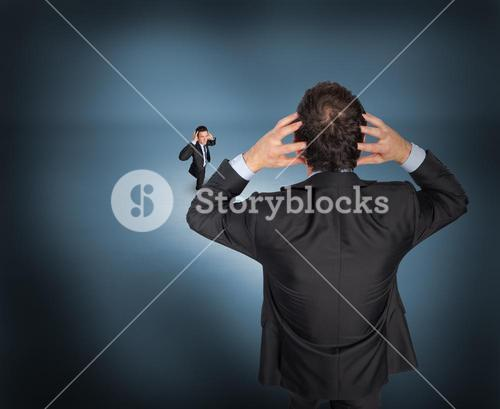 Composite image of stressed businessman with hands on head with tiny businessman