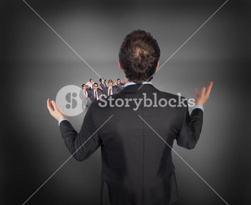Composite image of gesturing businessman with tiny businessmen