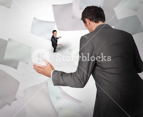 Composite image of businessman posing with hands out with tiny businessman