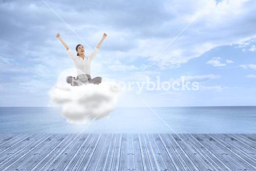 Composite image of cheering businesswoman sitting cross legged