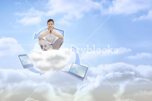 Composite image of businesswoman sitting cross legged with hands together