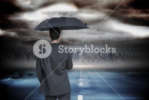 Composite image of rear view of classy businessman holding grey umbrella