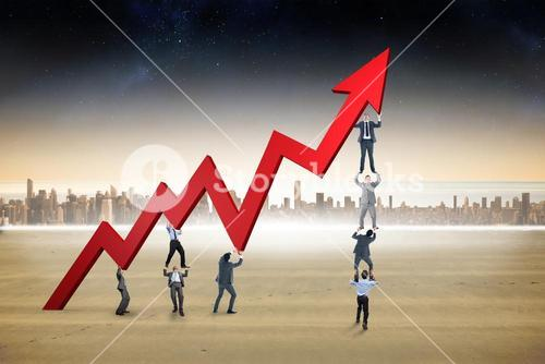Composite image of business team holding up arrow