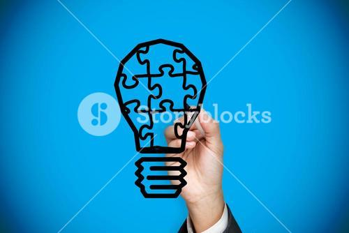 Composite image of businessman drawing light bulb