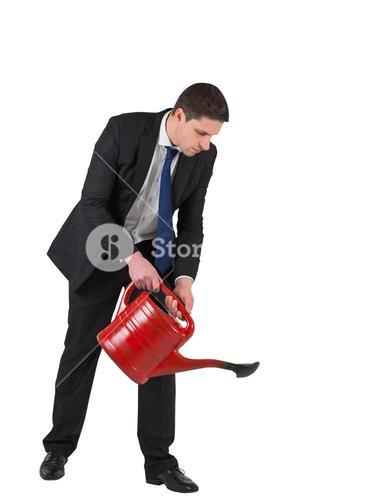 Businessman watering with red can
