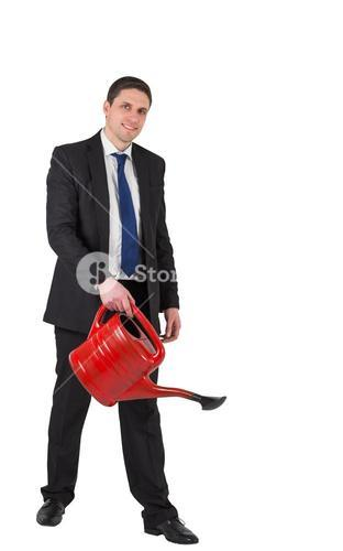 Businessman watering with red can and smiling at camera