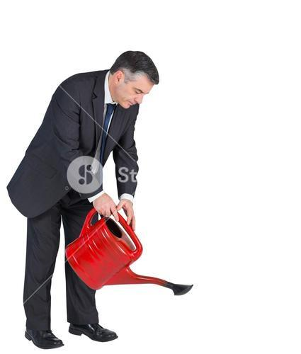 Mature businessman watering with red can