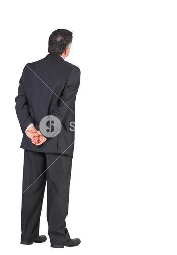 Mature businessman standing with hands behind back
