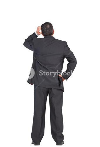Mature businessman standing and scratching head