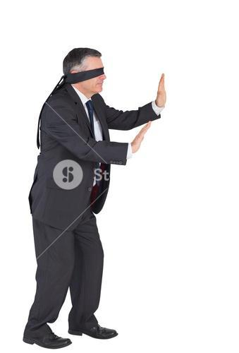 Mature businessman walking with blindfold