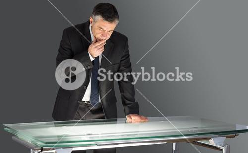 Concentrating businessman leaning on desk